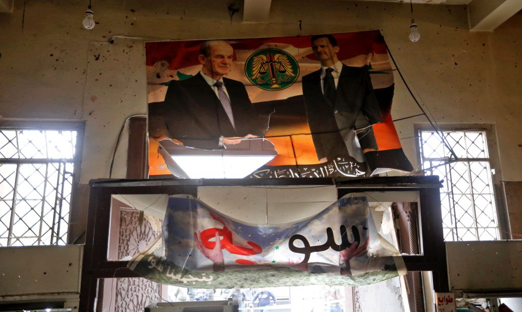 Portraits of Syrian President Bashar al-Assad (R) and his late father former president Hafez al-Assad are seen inside the old palace of justice building in Damascus following a reported suicide bombing on March 15, 2017. Two suicide bombings hit Damascus including the attack at the central courthouse that left at least 32 dead, as Syria's war entered its seventh year with the regime now claiming the upper hand. / AFP PHOTO / Louai Beshara (Photo credit should read LOUAI BESHARA/AFP/Getty Images)