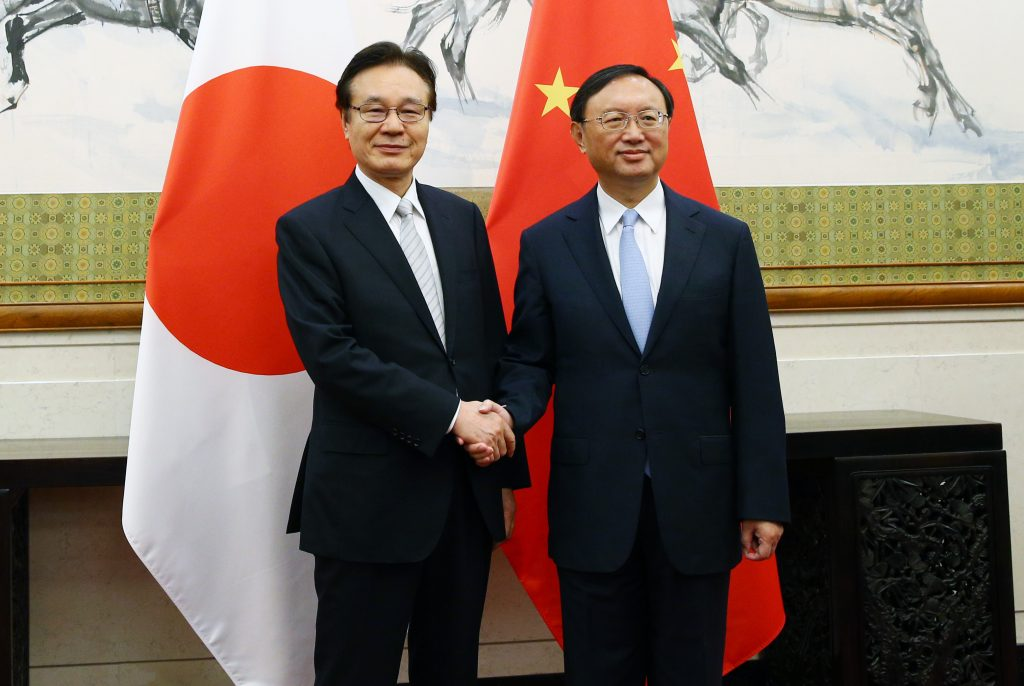 Japanese National Security Council chief Shotaro Yachi (L) shakes hands with Chinese State Councilor Yang Jiechi ahead of a meeting at the Diaoyutai State Guesthouse in Beijing on Aug. 25. WU HONG/AFP/Getty Images