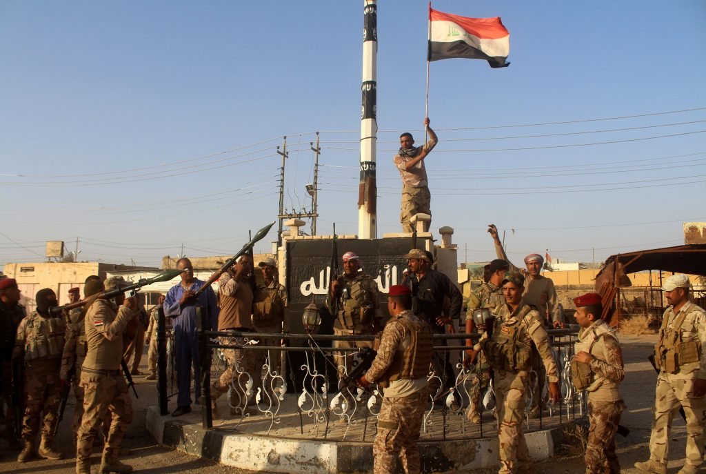 Iraqi government forces raise the Iraqi flag as they celebrate in the al-Bakr neighborhood north of Hit in Iraq's Anbar province after they cleared the area of IS fighters on Oct. 10, 2016. Iraqi security forces have launched a final push to retake Mosul from IS, which seized the country's second city more than two years ago. MOADH AL-DULAIMI/AFP/Getty Images