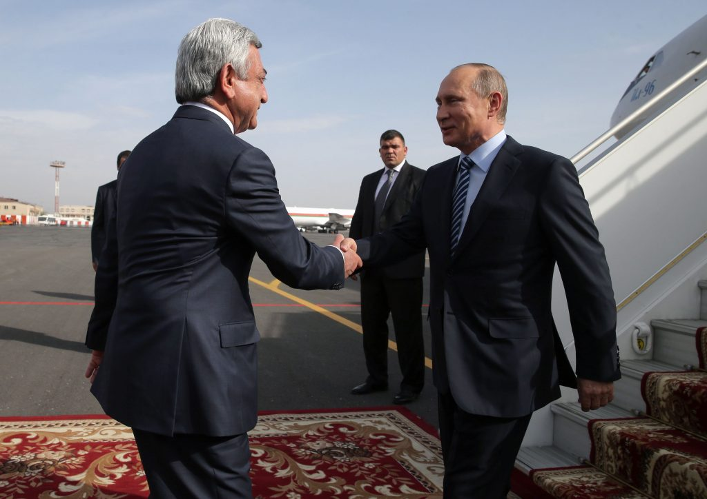 Russian President Vladimir Putin (R) shakes hands with Armenian President Serzh Sargsyan as he arrives at the Yerevan airport on Oct. 14, 2016. MIHAIL METZEL/AFP/Getty Images